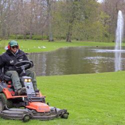 Copenhagen, Denmark - April 26, 2017: worker is cutting grass on lawn mower in park of Copenhagen, Denmark