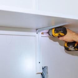 Man installing wooden shelves on brackets installation of shelves